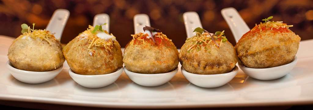 Pastry balloons of dahi puri, each filled with chickpeas, chutneys, and avocado, instead of the usual potato.