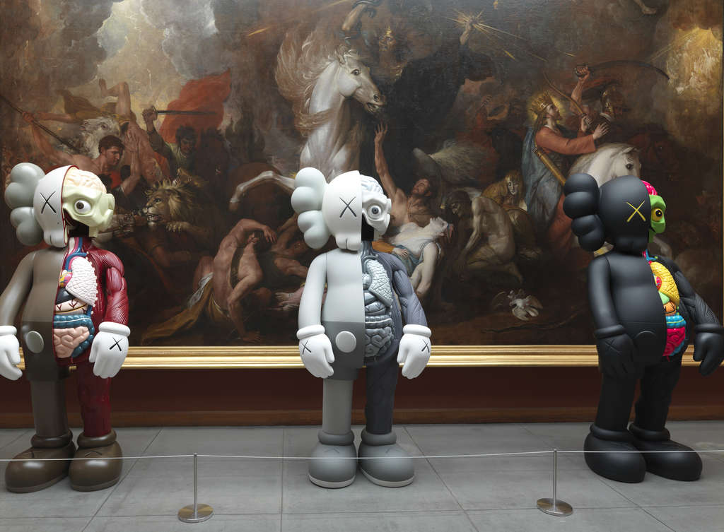 "At the Pennsylvania Academy of the Fine Arts, three ""Companion"" figures by KAWS stand guard before Benjamin West´s 1817 painting ""Death on the Pale Horse."""