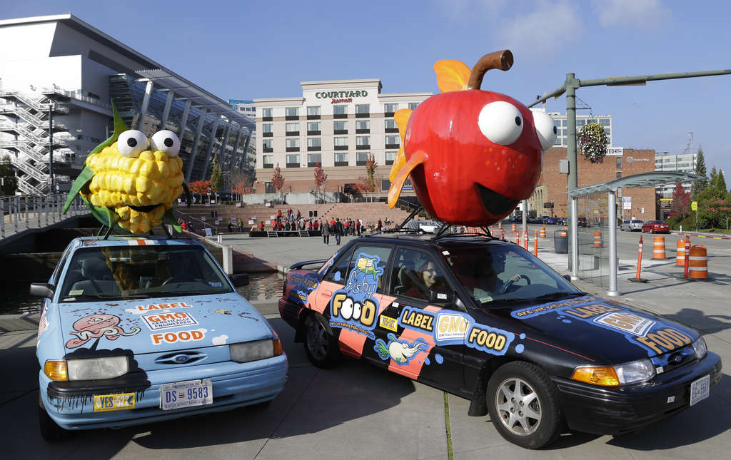"""Cars with a giant corn cob and a giant apple promote """"Yes"""" votes on the Washington state initiative to require labels on genetically engineered food. The referendum failed Tuesday."""