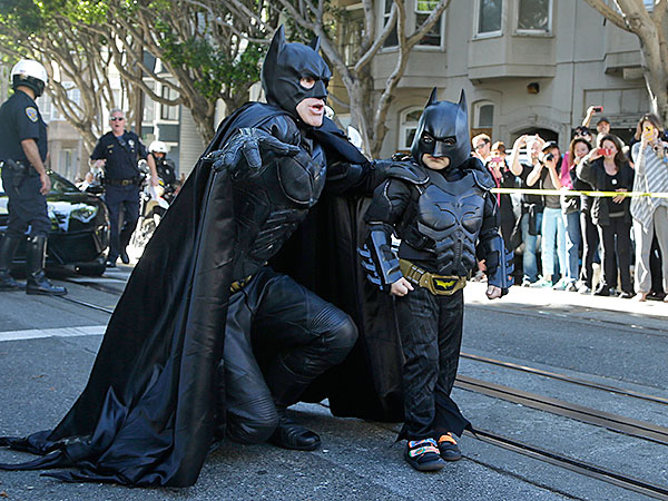 "Miles Scott, dressed as Batkid, right, walks with Batman before saving a damsel in distress in San Francisco, Friday, Nov. 15, 2013. San Francisco turned into Gotham City on Friday, as city officials helped fulfill Scott´s wish to be ""Batkid."" Scott, a leukemia patient from Tulelake in far Northern California, was called into service on Friday morning by San Francisco Police Chief Greg Suhr to help fight crime, The Greater Bay Area Make-A-Wish Foundation says. (AP Photo/Jeff Chiu)"