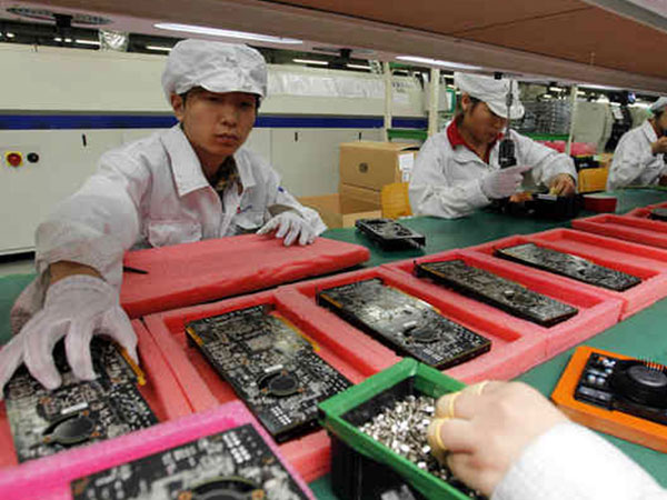 Staff members work on the production line at the Foxconn complex where iPhones and Dell computers are made. The company plans to do some manufacturing in the United States. (AP File Photo)