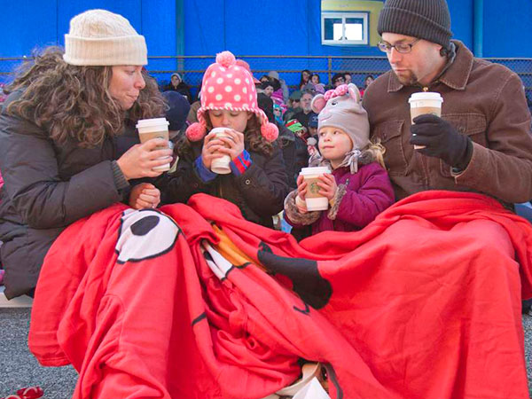 Bundled against the cold and sipping warm drinks while awaiting a Reindeer Party at Sesame Place are (from left) Lauren Einhorn of Ho-Ho-Kus, N.J.; daughters Cora, 6, and Brooke, 3; and husband Eric. (David M Warren / Staff)