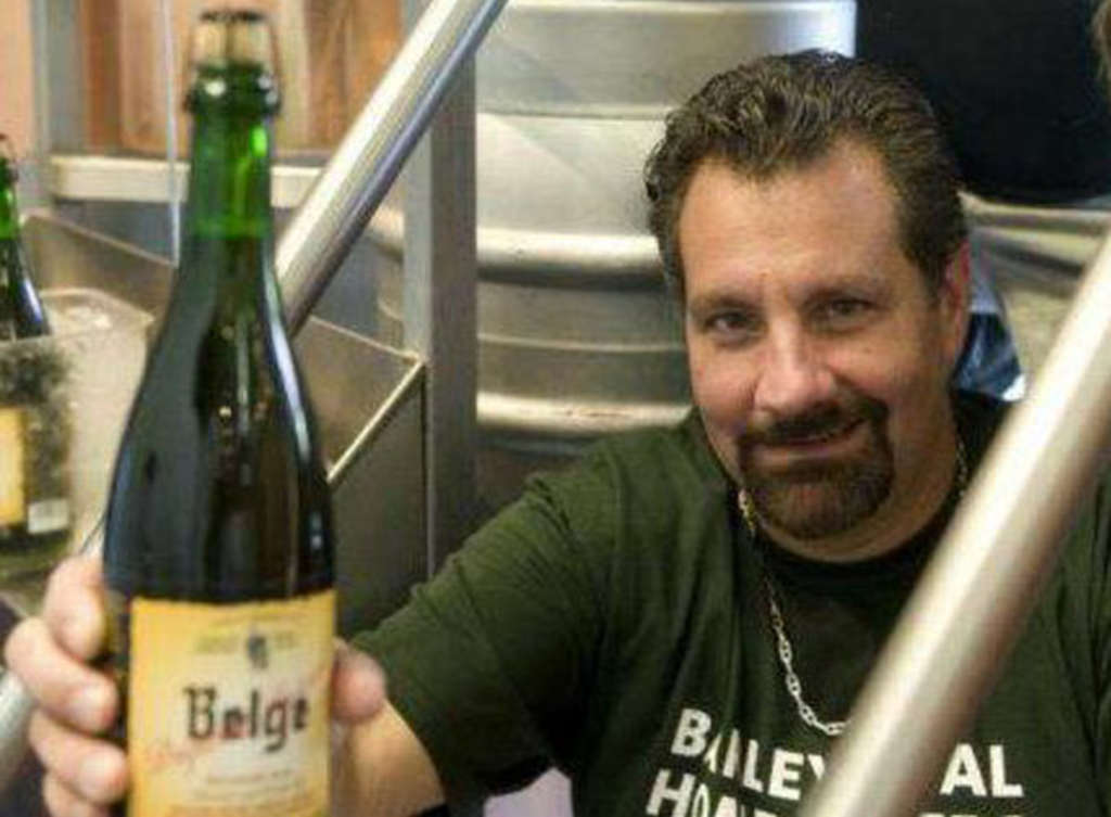 Vince Masciandaro hoists a bottle of Speciale Belge, the beer (with the trip that came along with it) that changed his life.