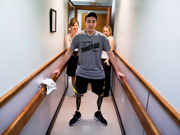The New York Times photographer Josh Haner´s image of Jeff Bauman is shown in this picture provided by the New York Times, which was part of his Pulitzer prize winning entry for feature photography announced by Columbia University in New York on April 14, 2014. In the image, Bauman, who lost his lower legs in the Boston Marathon bombings, walks on his own for the first time since the marathon at a final fitting for his prosthetic legs, in Massachusetts on May 31, 2013. The knees in his new legs have microprocessors that can be programmed to follow his gait, to swing as he steps. Behind Bauman is his girlfriend, Erin Hurley (L) and prosthetist, Julianne Mason.