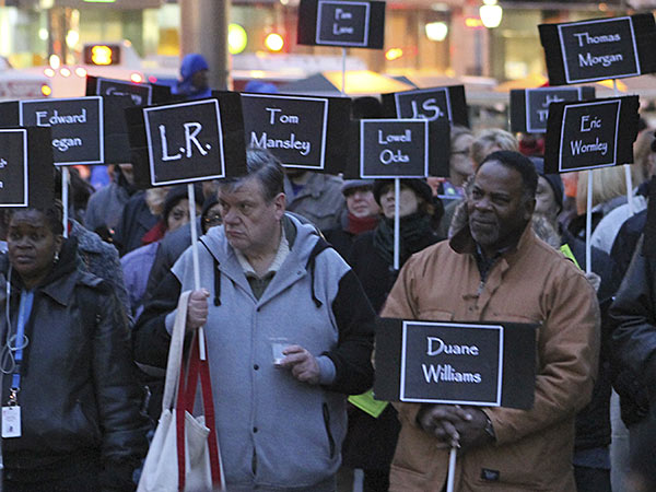 Advocates gather at the Homeless Memorial on Dec. 19, 2013, remembering the homeless and formerly homeless who have lost their lives. Each sign held aloft represents someone who passed away. Exposure to extreme weather is a leading cause of death for those on the streets.