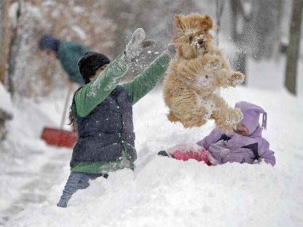 Lindsay Knutson, left, plays in the heavy snow with her family dog, Aspen, and daughter Flora Bejblik, 4, as her husband Bob Bejblik, rear left, shovels.<br /><br /><br />