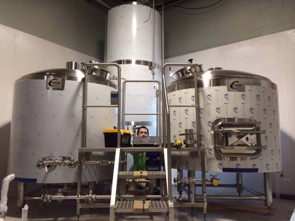 Head brewer Andrew Horne amid Conshohocken´s 15 bbl (465 gallons) brew kettle on the left, 15 bbl mash tun on the right and 30 bbl hot liquor (water) tank in the back.