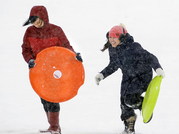 Ama Liew and Vivian Le, students at Massachusetts College of Pharmacy and Health Sciences University, enjoy sledding at Quinsigamond Community College in Worcester, Mass. on Thursday, Feb. 13, 2014.  They initially came to the hill with cardboard and garbage bags; they left and returned with these real sledding saucers.  (AP Photo/Worcester Telegram & Gazette, Christine Peterson)