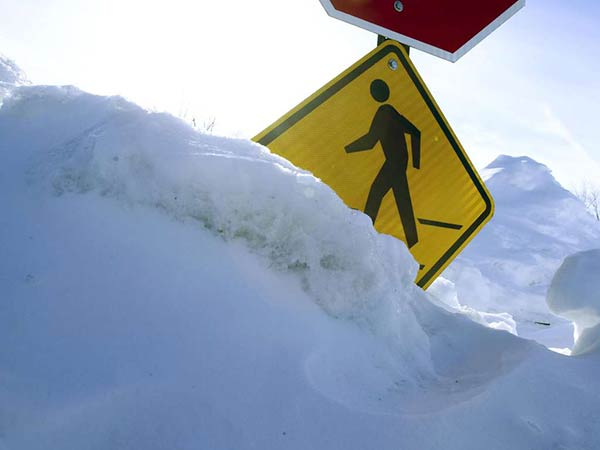 A school crosswalk sign at Lansdale Catholic High School is mostly buried with snow. DAVID M WARREN / STAFF PHOTOGRAPHER