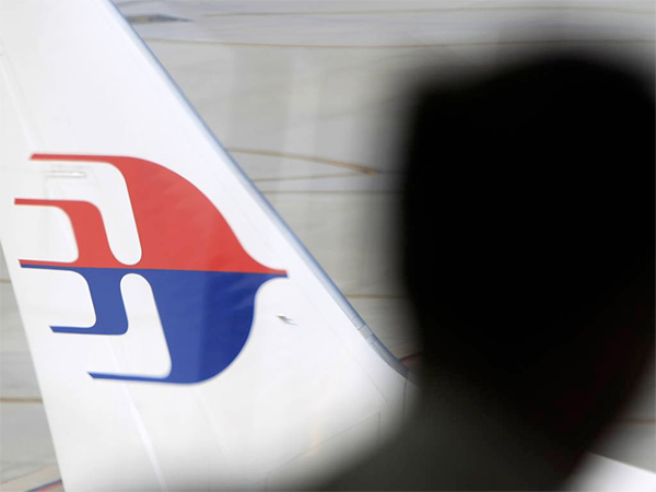 A man looks out from a viewing gallery as a Malaysia Airlines aircraft sits on the tarmac at Kuala Lumpur International Airport in Sepang, Malaysia, Sunday, March 9, 2014. (AP Photo/Lai Seng Sin)
