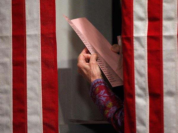 A woman reads a ballot before casting her vote. (AP file)