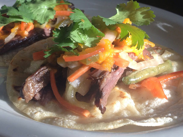 """The Champion"" has Asian style braised rib cap with giardinera (carrots, onions, red bell pepper, cucumber, green beans, olives, jalepenos, pickled in red wine vinegar and oil) on a corn tortilla."