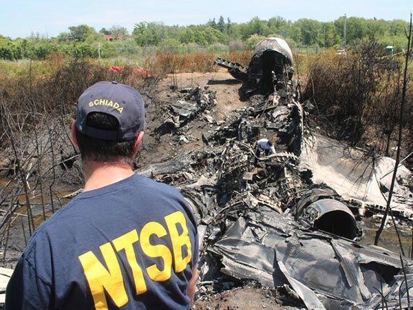 Federal investigators Luke Schiada and Pete Wentz search the wreckage of Gulfstream IV jet crash in Bedford, Mass. that killed Philadelphia philanthropist and businessman Lewis Katz and six others. (Credit: NTSB Twitter account)
