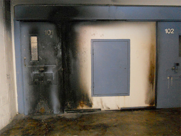 The charred door frame of a solitary-confinement unit. Former inmates said that prisoners housed in such units sometimes started fires in an effort to attract the attention of guards.