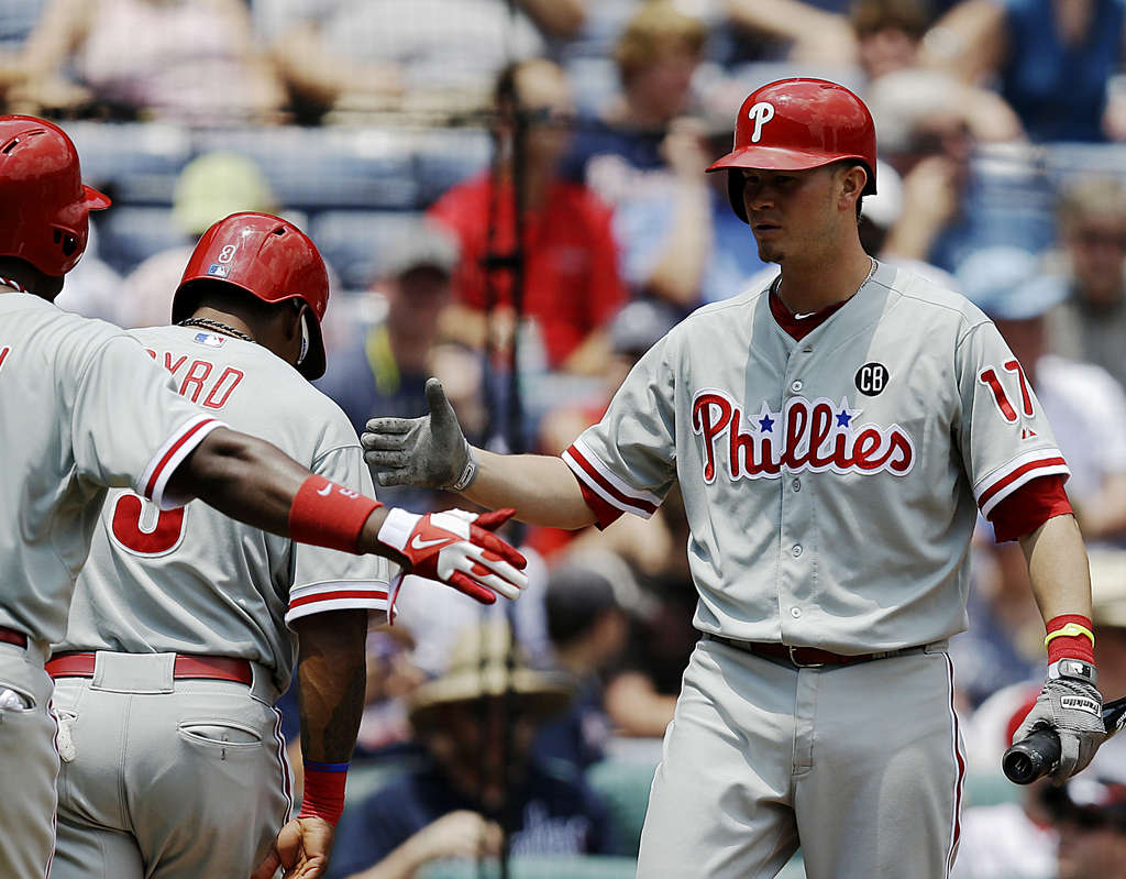ASSOCIATED PRESS Phillies´ Reid Brignac (right) congratulates Marlon Byrd and Domonic Brown, who scored on a single by John Mayberry Jr. in second inning against Braves yesterday.