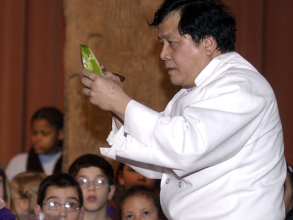 Joe Poon, knife in hand, creating a likeness of Elvis Presley from watermelon rind.