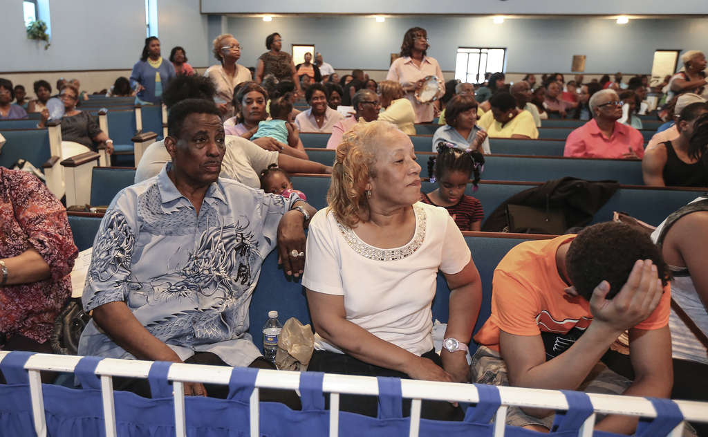 STEVEN M. FALK / STAFF PHOTOGRAPHER Bishop Barry Connelly with his wife, Doris, attend a tribute on Tuesday for their son Eugene, who was fatally shot June 24. Connelly lost his brother in a 1968 murder that went unsolved. This time he hopes witnesses step up.