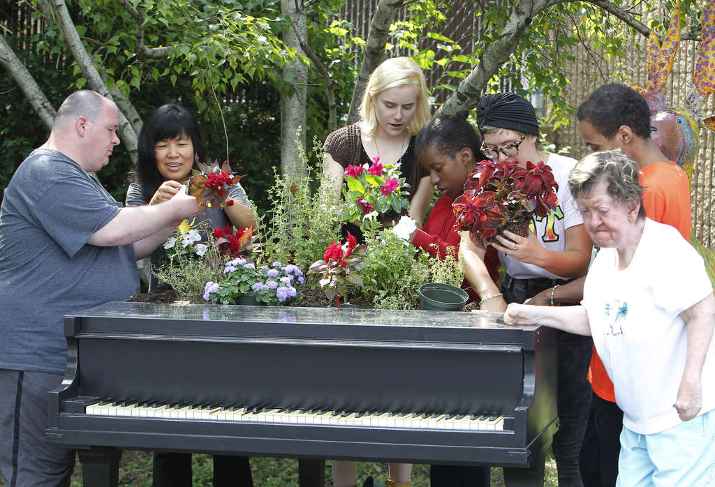 "Gather round the piano: (from left) Michael Merrinan, Meei-Ling Ng, staffer Jennifer Pague, Kia Heidon, staffer Karly Smith, Rodney Harris, and Monica Maye plant flowers for ""Musical Garden"" at SpArc Services in Tioga, which provides vocational training and job opportunities to intellectually and physically disabled adults."