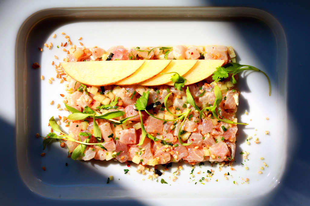 A marinated hamachi tartare is Asian-inspired with cilantro, toasted sesame, lime zest, and furikake spice. Hints of nuttiness and citrus mingle with sweet apples and crunchy shallots atop the raw fish. No two bites are exactly the same.