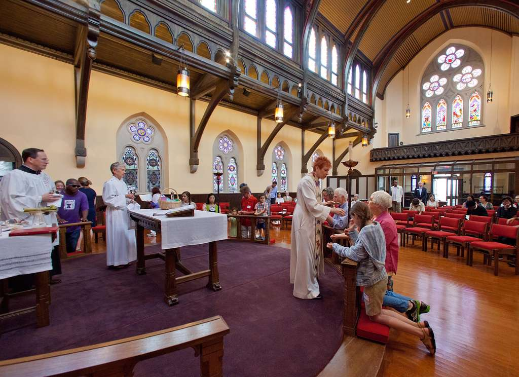 The Rev. Donna Maree offers communion on the 20th anniversary of a lightning strike at Trinity Memorial Church.