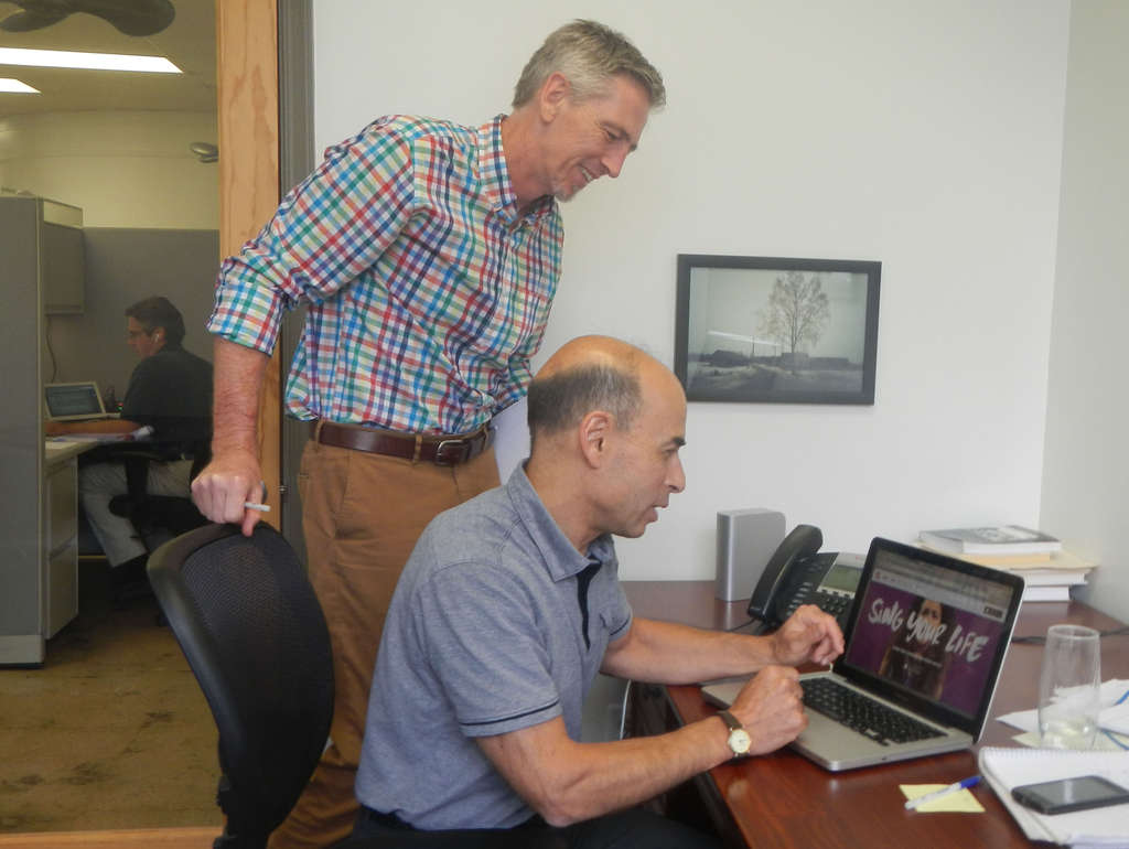 MuseAmi chief operating officer Ed Hynes (left) and CEO and founder Bob Taub look at a page from Hook´d, an app that was launched July 10, in the company´s office in Princeton.