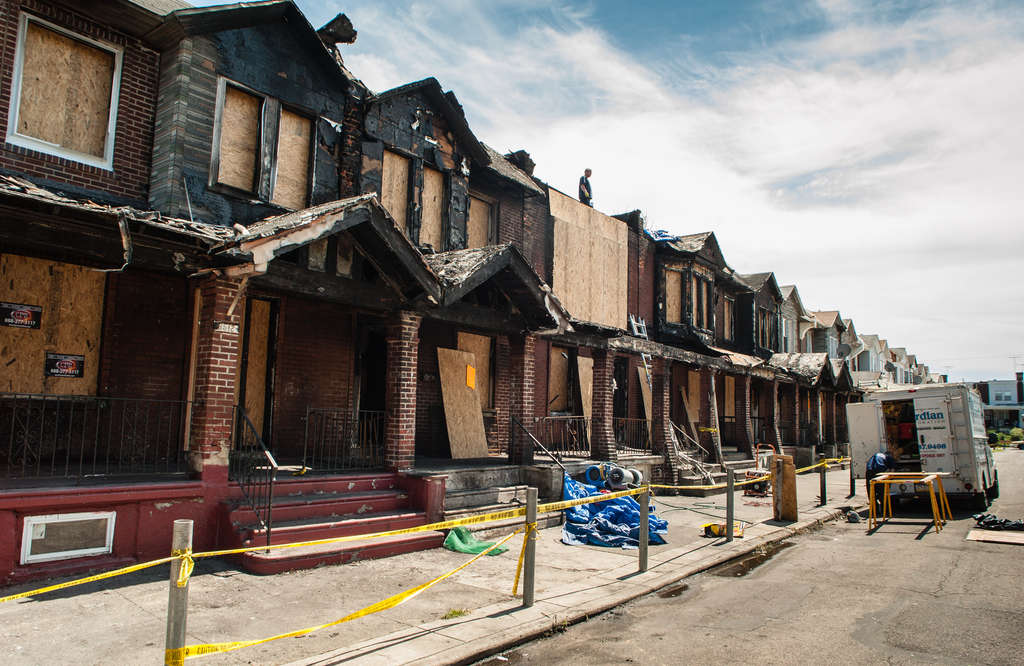 MATTHEW HALL / STAFF PHOTOGRAPHER Cleanup begins on Gesner Street the day after a fire damaged eight rowhouses and killed four young children. The Fire Department´s investigation has turned up no answers as to what started the fire.
