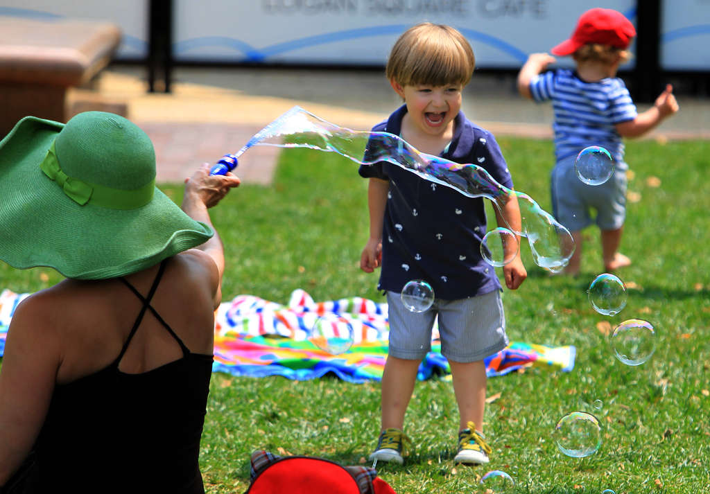 James Fike (center) playing in bubbles with his mother Denise Fike at Sister Cities Park this summer. The city´s property tax abatements attract families, but drain the schools of revenue.