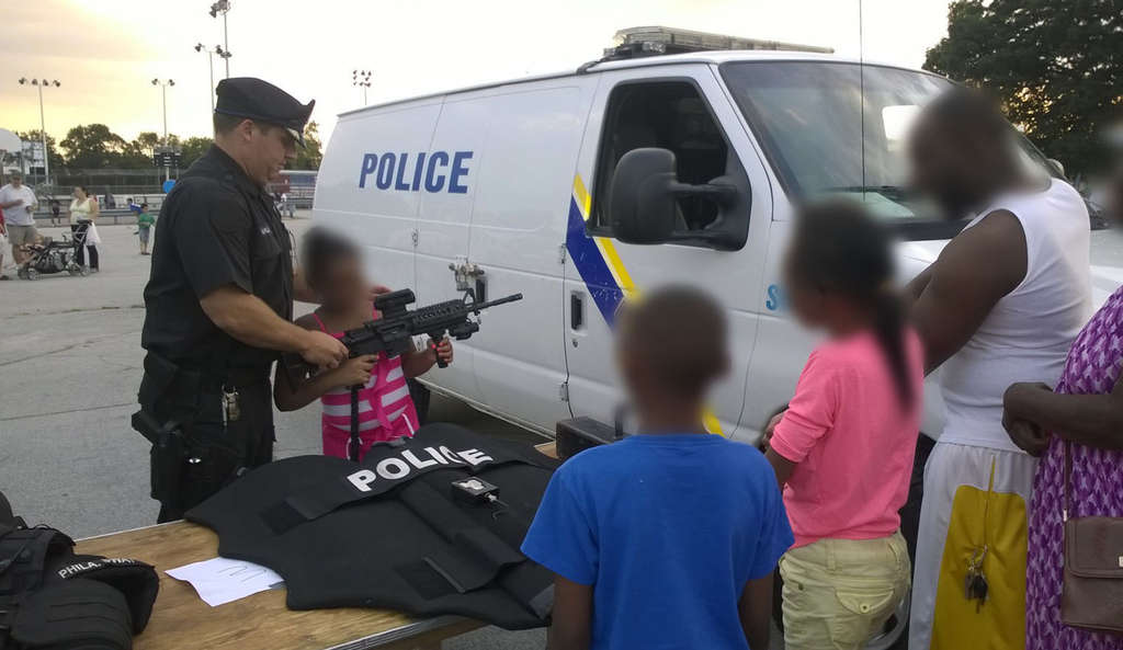 PHOTO COURTESY OF MARION BROWN An police officer helps a child handle a semiautomatic rifle at the Fox Chase Community Night Out last month.