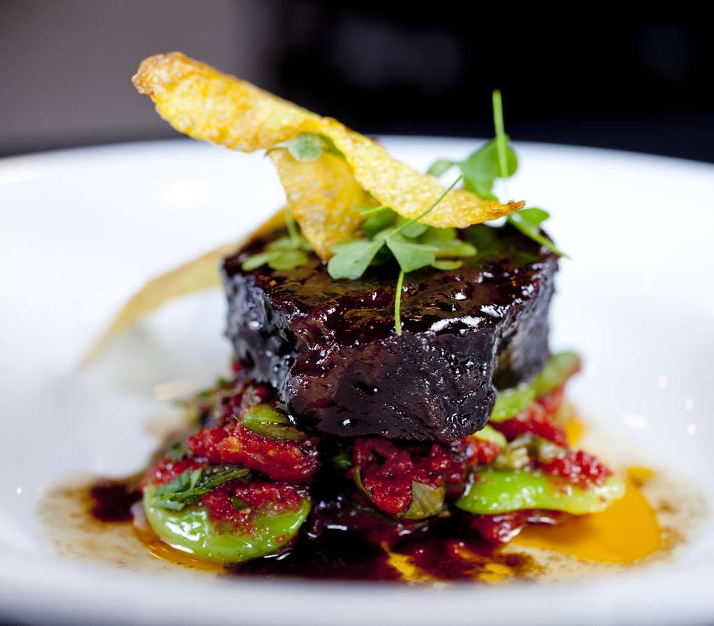 Slow-cooked beef cheek, meltingly tender over lima beans, heirloom tomato, sorrel, and saffron potato chips.