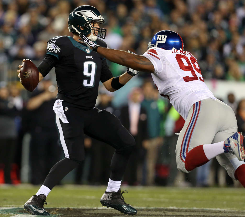 DAVID MAIALETTI / STAFF PHOTOGRAPHER Nick Foles backs away from the outstretched arms of the Giants´ Cullen Jenkins in shutout win.