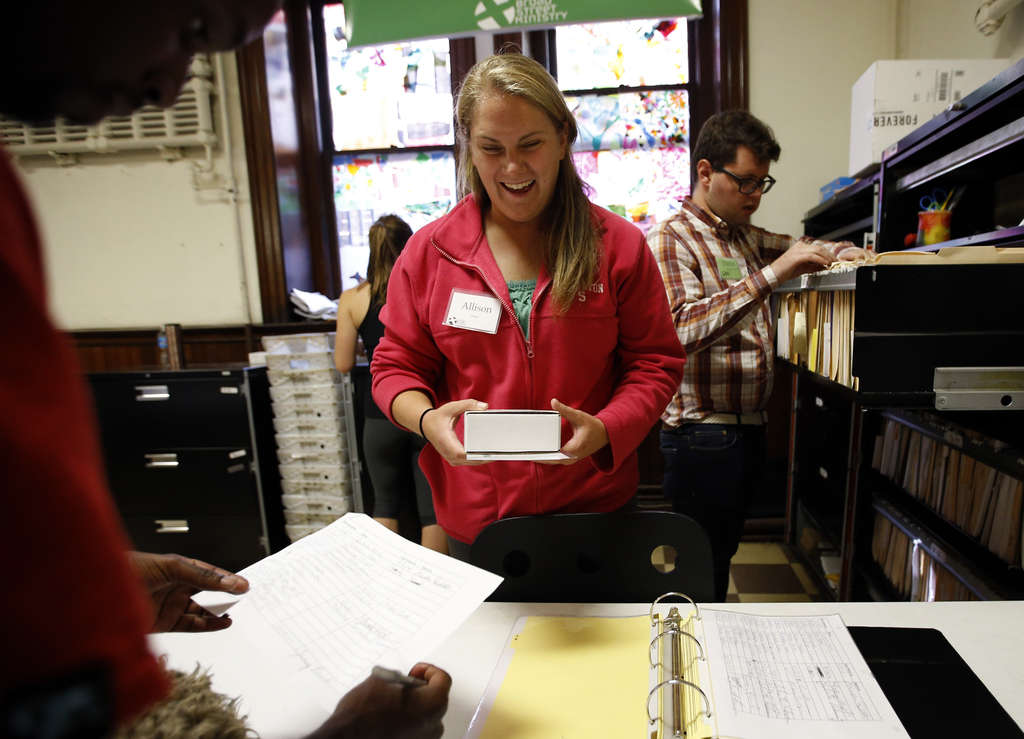 YONG KIM / STAFF PHOTOGRAPHER Volunteer Allison Davis helps hand out mail at the Broad Street Ministry, which allows the homeless to use its mailing address.
