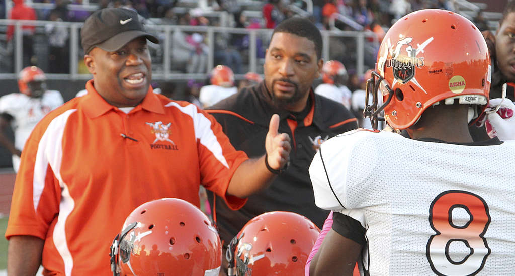 """First-year Del-Val Charter coach Troy Gore (left) talks to his players. """"I wanted to change the way the kids walked, the way they talked, the way they looked at academics, and the way they conducted themselves on the field,"""" Gore said. CHRIS PROCTOR"""