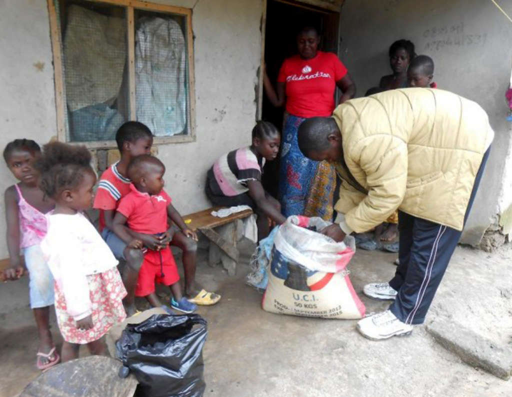 Wilfred Kokeh distributes food outside Ganta, Liberia. He is the Ganta-based field officer for , which has trained 20,000 Liberian women in leadership skills in the last six years. Women´s Campaign International
