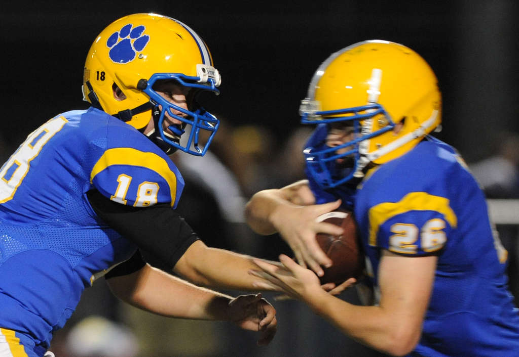 Downingtown East quarterback Andrew Hudson , handing off to Jack Kincade, will lead the Cougars offense against rival Downingtown West.        BRADLEY C. BOWER / For The Inquirer