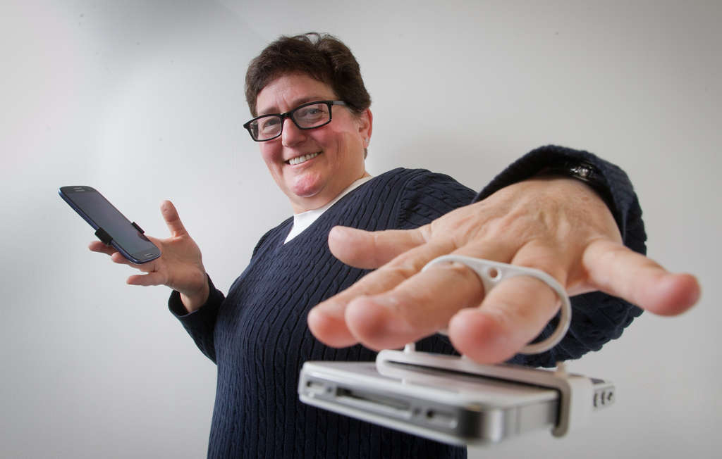 ALEJANDRO A. ALVAREZ / STAFF PHOTOGRAPHER Marjie Krupnick , founder of Maxxable, demonstrates how the clip keeps a smartphone secure.