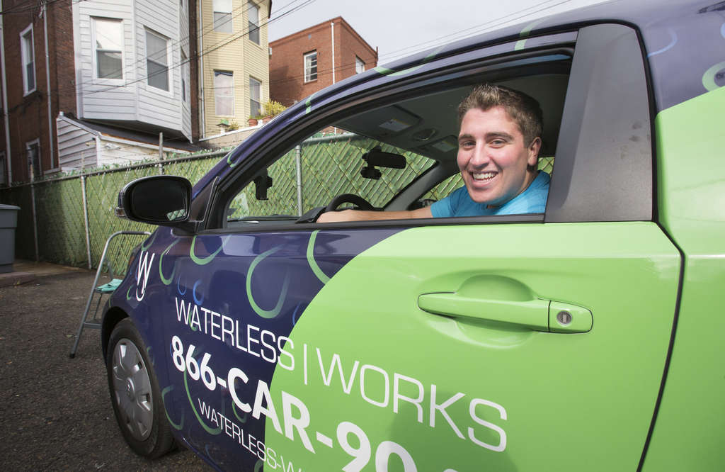 "JESSICA GRIFFIN / STAFF PHOTOGRAPHER Christopher Caporale, 21, founder of Waterless Works, with his waterless car cleaning-solution vehicle. Caporale´s goal is for his five-person startup to be the ""Uber of car wash."""