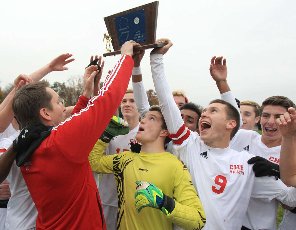 Celebrating the sectional title, coach Jason Meile (left) holds up the Pirates´ Group 2 trophy.