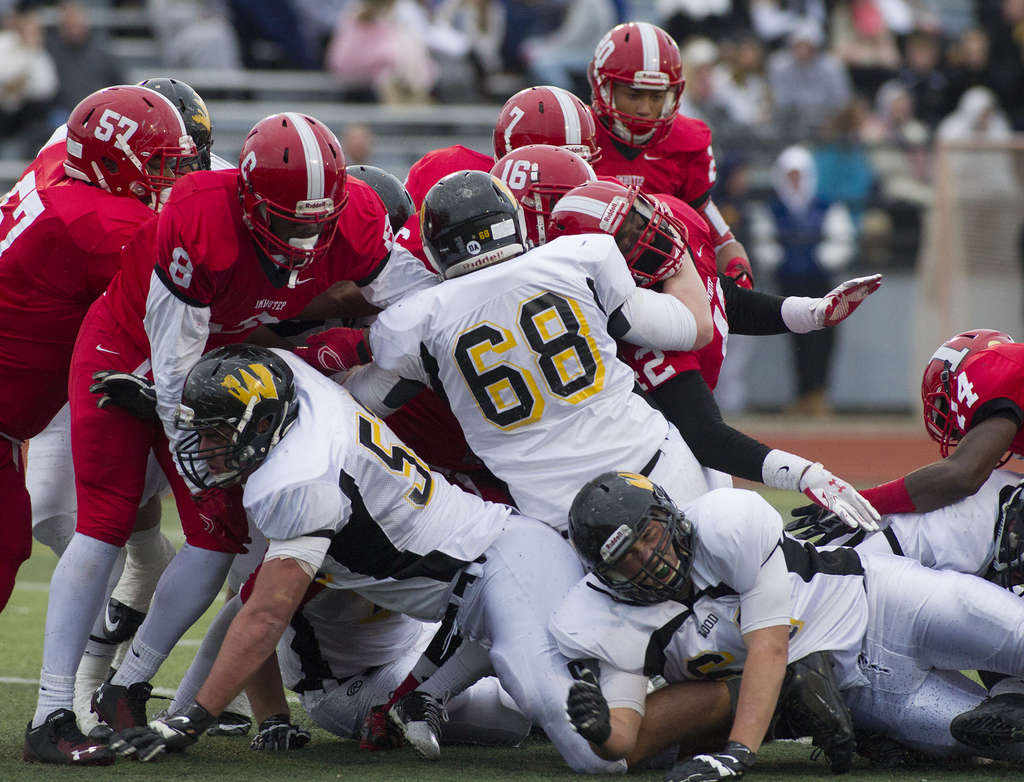The bodies are piled high, but somewhere on the bottom is Wood quarterback Anthony Russo, who scored a two-point conversion in the first half vs. Imhotep.