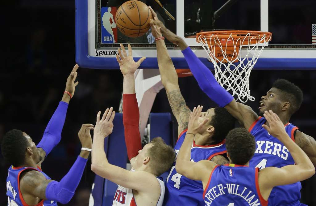 The 76ers´ K.J. McDaniels (14) rejects a layup by Detroit´s Kyle Singler, with help from Nerlens Noel (right) as Robert Covington (left) and Michael Carter-Williams close in during the game on Saturday. The 76ers beat the Pistons, 108-101.