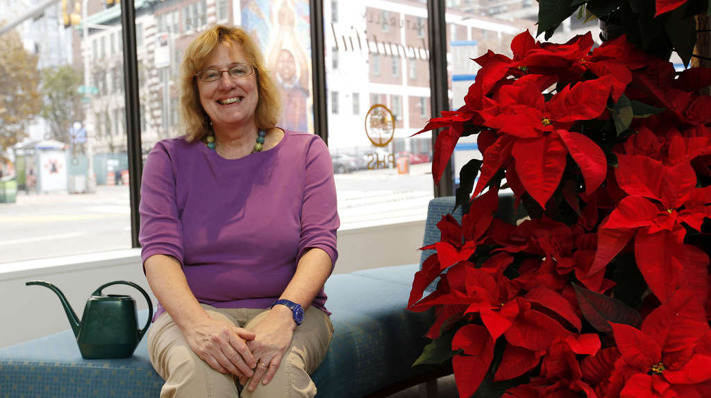 Janet Evans, senior manager at the Pennsylvania Horticultural Society´s McLean Library, sits outside the exhibition of poinsettia plants.
