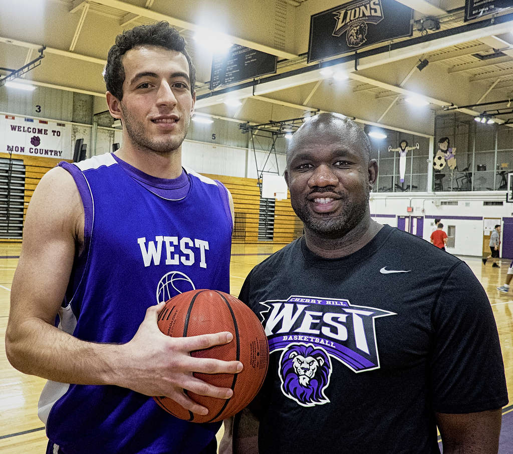 Cherry Hill West´s Can Oztamur , with coach Hamasi Tarrant. This season West and East are rated 9th and 10th, respectively, in The Inquirer´s preseason boys´ basketball poll. ED HILLE / Staff Photographer