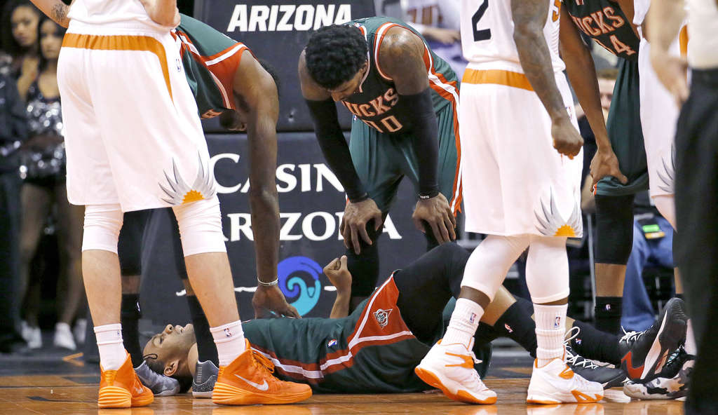 ASSOCIATED PRESS Bucks rookie Jabari Parker waits for help on the court after knee injury.