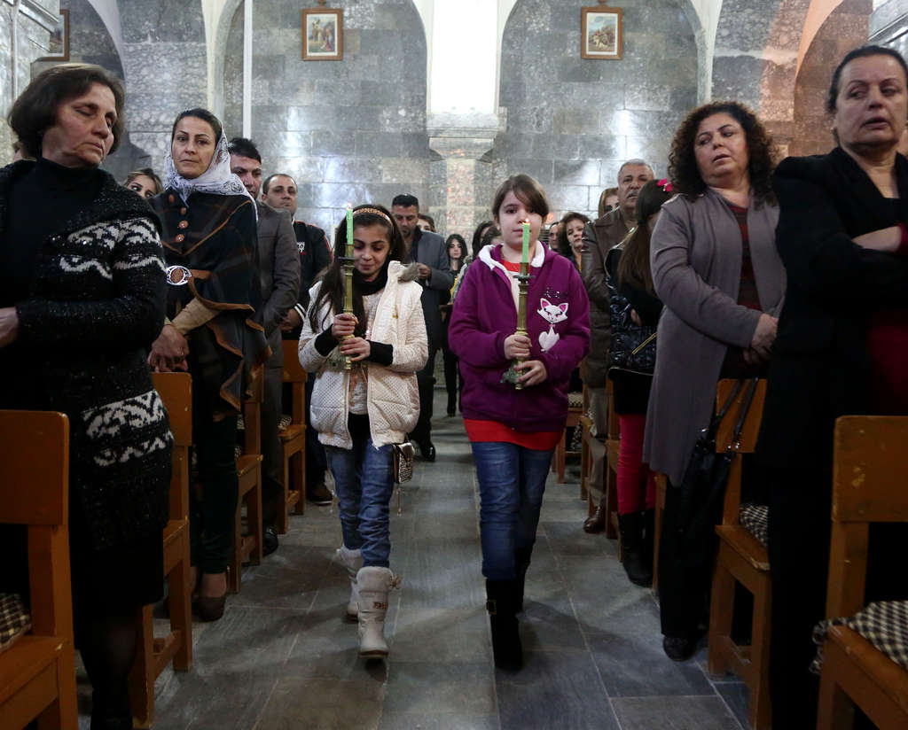 Iraqis at Christmas Eve Mass in the Chaldean Church of the Virgin Mary in al-Qoush, near the battle lines with ISIS.