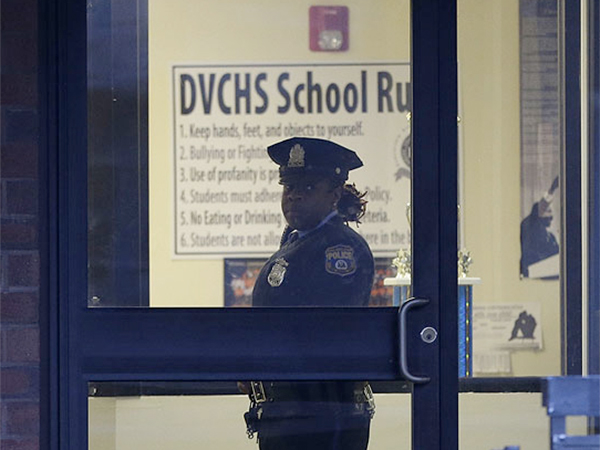 Police stands guard the Delaware Valley Charter School Friday, Jan. 17, 2014, in Philadelphia, after two students were shot. The District Attorney's Office has approved aggravated assault charges for one teen suspected in a shooting Friday at Delaware Valley Charter High School that wounded two students. (AP Photo/Matt Rourke)