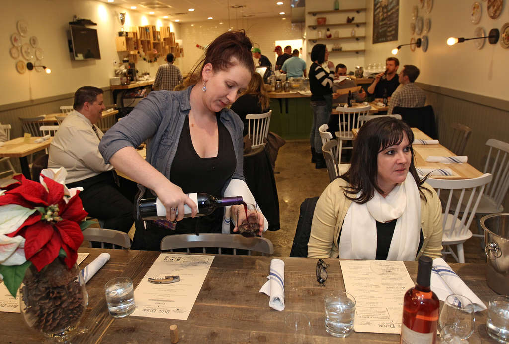 Server Alicia Bodner pours the wine for a party seated at the big community table at the front of the Blue Duck Sandwich Company.