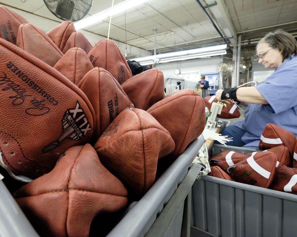 Official game balls for Super Bowl XLIX wait to be laced at the Wilson Sporting Goods Co. in Ada, Ohio. Game officials check the footballs two hours before a game, but then give them back to the teams.