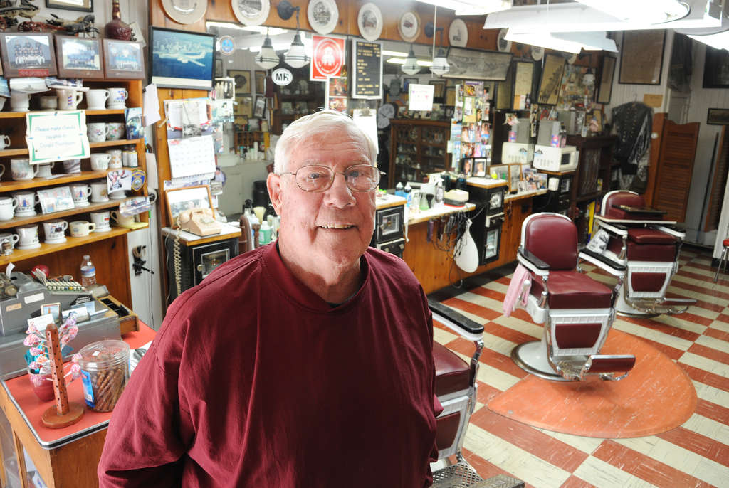 PHOTOS: CLEM MURRAY / STAFF PHOTOGRAPHER Don Thompson at his barbershop in Mount Holly, where even the cash register goes back to simpler times.