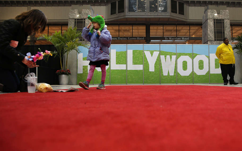 """Caroline Perner and daughter Margaret, 6, are flanked by a replica of the famed """"Hollywood"""" sign at the Flower Show; at left, Jim Ethridge, of Middletown, Del., takes a photo of some furry green guy made of flowers."""