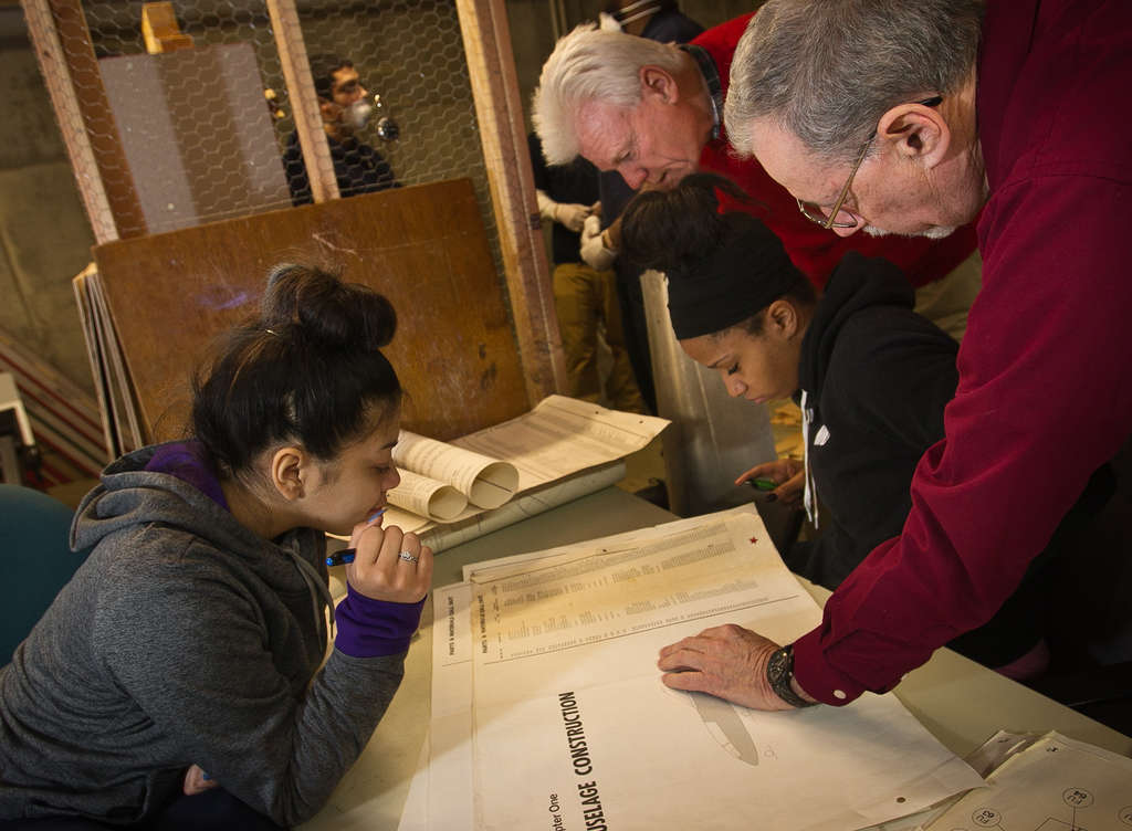 In a program to broaden horizons, students in Camden are building a plane from a kit. Ashley Gascot (left) and Ashley Williams look over an inventory list with Ira Weissman (foreground) and Don Powell.