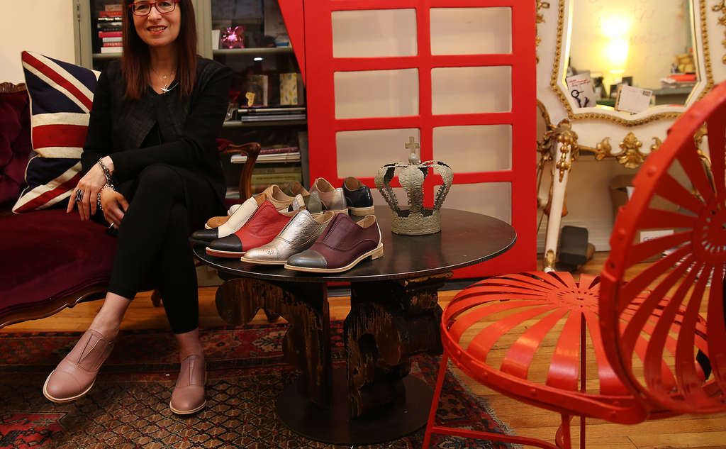 DAVID MAIALETTI / STAFF PHOTOGRAPHER Elena Brennan , owner of Bus Stop shoe boutique, sits near a sample of her line, Bus Stop x All Black.